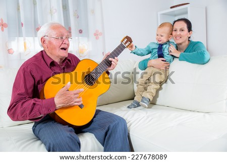 Grandfather playing the guitar to his grandson - stock photo