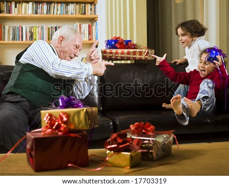 grandfather playing with grandchildren with presents - stock photo