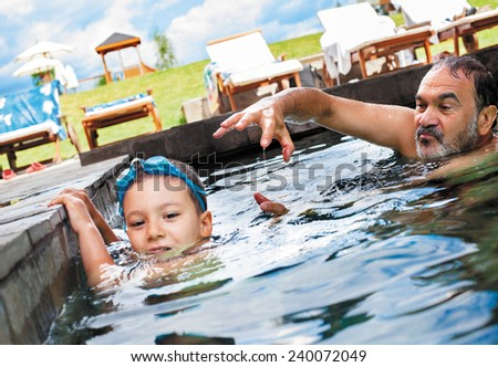 grandfather playing with his grandson in an outdoor pool. - stock photo