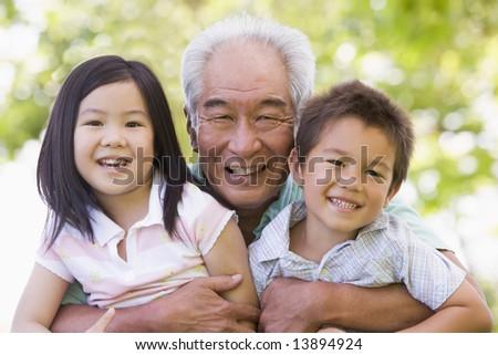 Grandfather posing with grandchildren - stock photo