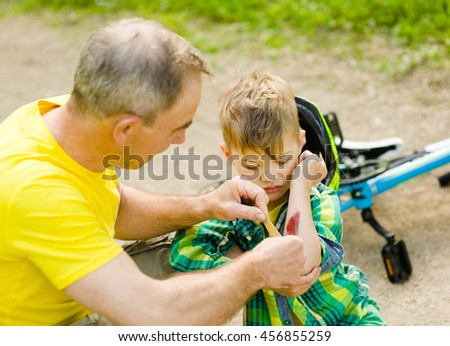 Grandfather putting band-aid on young boy's injury who fell off his bicycle. - stock photo