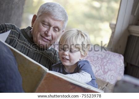 Grandfather reading a book to his grandchild - stock photo