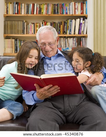 grandfather reading a story to his grandchild - stock photo