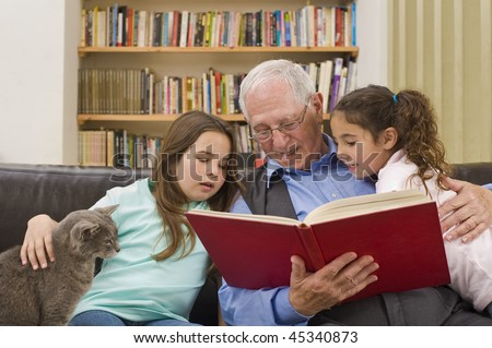 grandfather reading a story to his grandchild with a cat