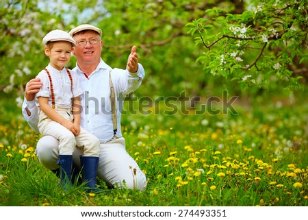grandfather sharing experience with grandson in spring garden - stock photo
