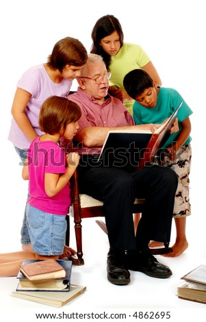 Grandfather sharing photo albums with four of his grandchildren.  Isolated on white. - stock photo
