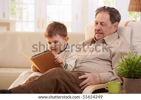 Grandfather sitting in armchair at home, holding his grandson who looking pictures in book.