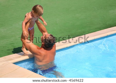 Grandfather standing in pool holds on hands granddaughter