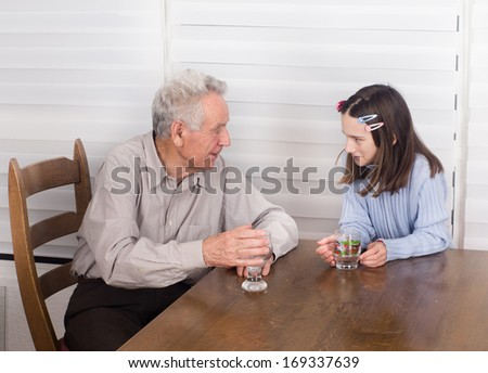 Grandfather talking and smiling with his granddaughter at table - stock photo