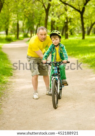 Grandfather teaches his grandson to ride a bike