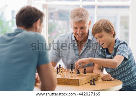 Grandfather teaching grandson how to play chess. Father and son playing chess with grandchild. Grandfather watching son and grandson playing board game at home. - stock photo