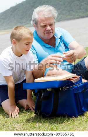 grandfather teaching grandson how to prepare fishing tackles - stock photo