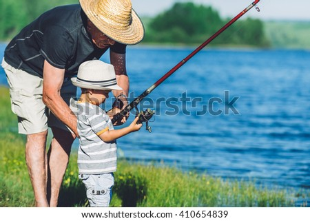 Grandfather teaching his grandson how to fish