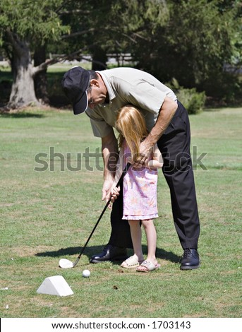 Grandfather teaching his young grand-daughter how to hold a golf club. - stock photo