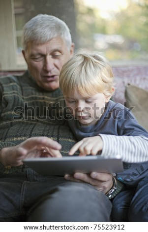 Grandfather using touchscreen tablet PC with grandson - stock photo