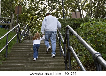 Grandfather walking child up concrete stairs at a park. - stock photo