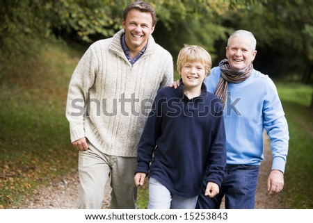 Grandfather walking with son and grandson along autumn path - stock photo