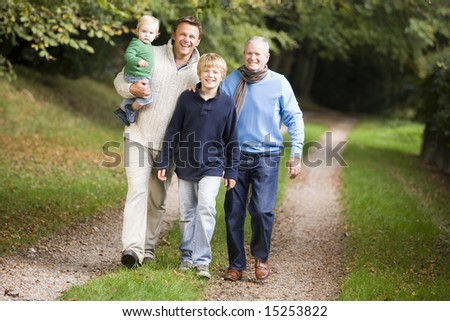 Grandfather walking with son and grandson along woodland path - stock photo