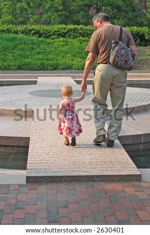 Grandfather walks across plaza with precious granddaughter - stock photo