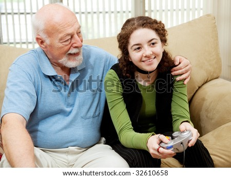 Grandfather watching teen granddaughter play video games. - stock photo