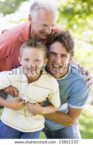 Grandfather with adult son and grandchild in park - stock photo