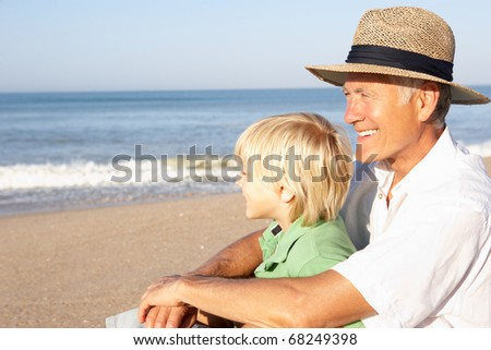 Grandfather with child on beach relaxing - stock photo