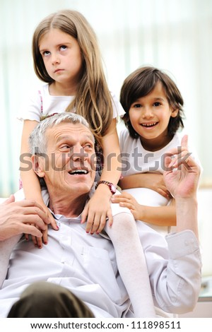 Grandfather with children at home - stock photo