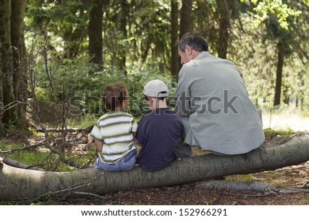 Grandfather with children sitting and resting on a log in forest.