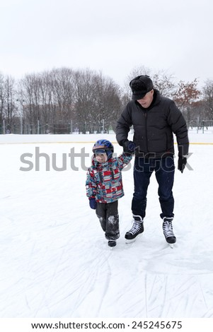 Grandfather with grandchild playing at the skating rink - stock photo