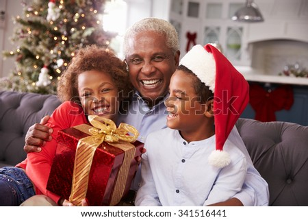 Grandfather With Grandchildren Opening Christmas Gifts - stock photo