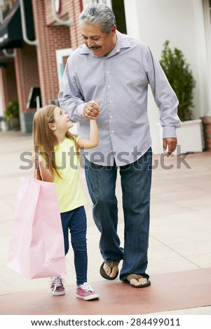Grandfather With Granddaughter Carrying Shopping Bags