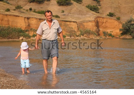 Grandfather with granddaughter goes as to water on beach - stock photo