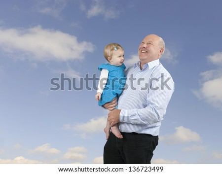 grandfather with granddaughter, outdoors against a blue sky with clouds - stock photo