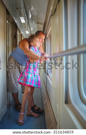 Grandfather with granddaughter stand in corridor coupe and look through window - stock photo