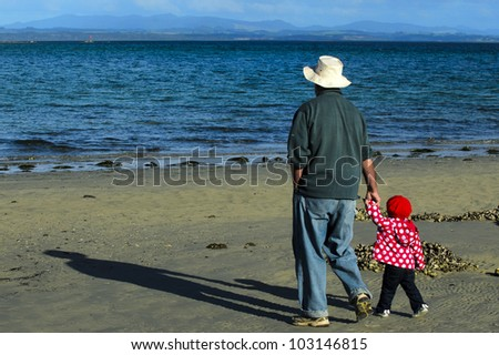 Grandfather with granddaughter walks on the beach during winter. Concept photo of grandparents, grandfather, grandad, ,grandchild, childhood, granddaughter, relationship, lifestyle,family, education. - stock photo