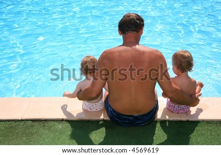 Grandfather with granddaughters seats aboard of pool - stock photo