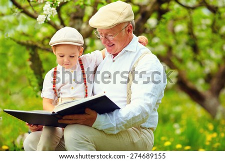 grandfather with grandson reading book in spring garden - stock photo