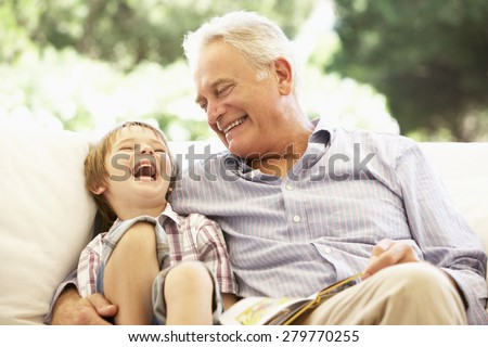 Grandfather With Grandson Reading Together On Sofa - stock photo