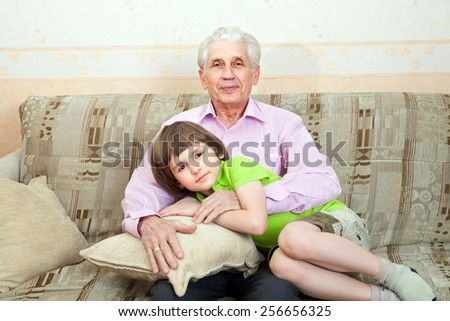 Grandfather with grandson sit on couch together - stock photo
