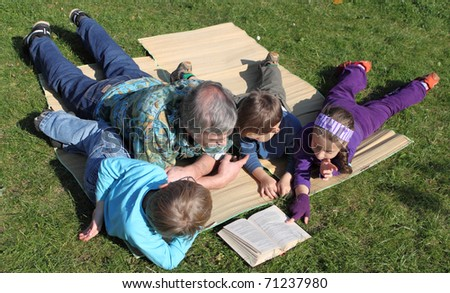 grandfather with his grandchildren read fairy tales lying on the grass - stock photo