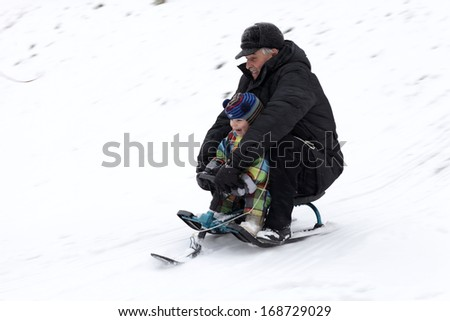Grandfather with his grandson ride a sled from a hill - stock photo