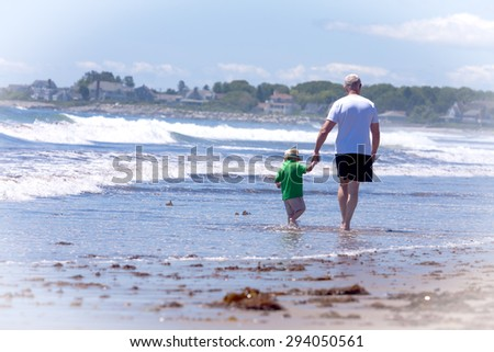 grandfather with his grandson walking on a beach on a sunny day - stock photo