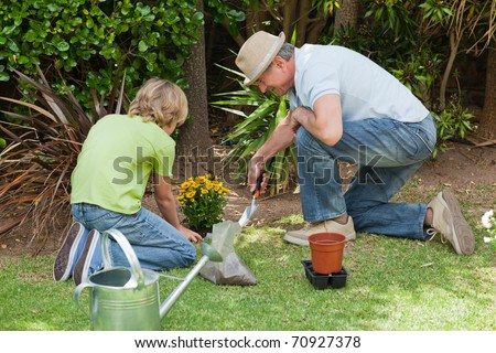 Grandfather with his grandson working in the garden - stock photo