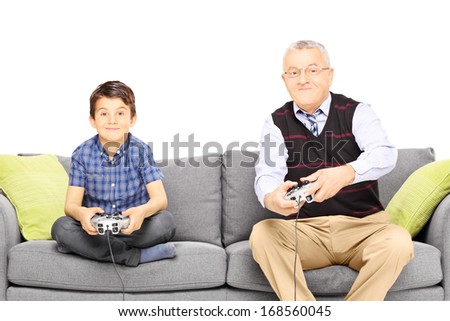 Grandfather with his nephew seated on a modern sofa playing video games isolated on white background - stock photo