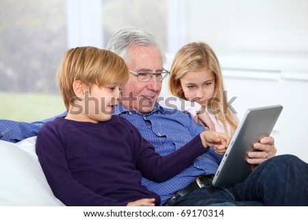 Grandfather with kids using electronic tab - stock photo