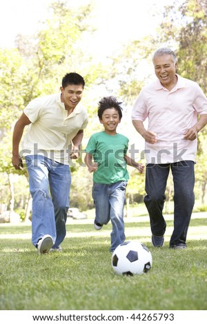 Grandfather With Son And Grandson Playing Football In Park - stock photo