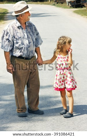grandfather with the granddaughter go on the road - stock photo