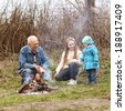 Grandfather with two grandchildren sitting around the campfire. Grandfather and grandchild - stock photo
