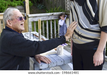Grandfather (95 years old) holds his pregnant granddaughter abdomen while her daughter is sad in the background. Concept photo of pregnancy, pregnant woman family lifestyle.