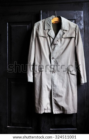Grandfathers vintage raincoat on a wooden hanger on a black wardrobe